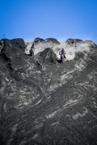 Two Enduro Riders racing downhill in the black lava at Batur volcano in Bali